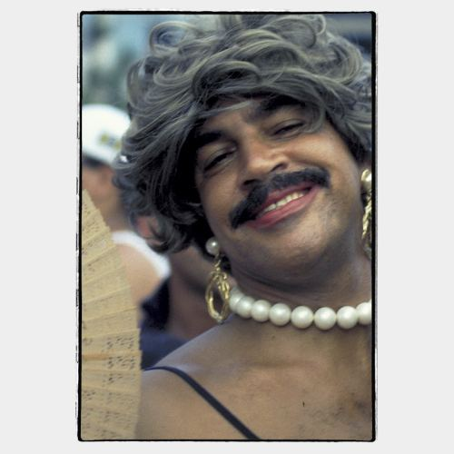 Rio Carnival: happy expression on face of man with woman make up and big moustache