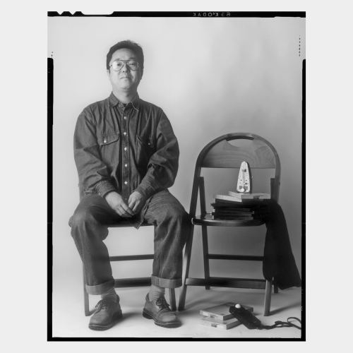 Japanese male artist sitting on chair with props